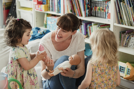 Mother and her two daughters are looking at a toy baby doll and talking about giving it a bottle. The mother is holding the doll baby and passing her daughter the toy baby bottle. Stock Photo