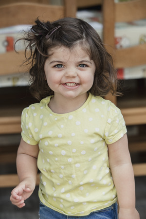 Front view of a little girl standing indoors, looking at the camera and smiling for a headshot. The little girl is wearing casual clothing.
