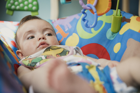 Low angle, close-up view of a baby girl lying in a baby bouncer relaxing.