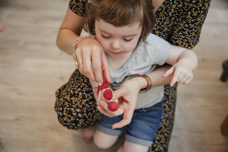 Front view of a little girl playing with some raspberries and putting them onto her fingers. Her mother is kneeling behind her helping and laughing with her.