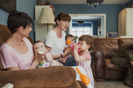 Side view of two mothers sitting on a a sofa in a living room. One mid adult woman is feeding her baby with a bottle of milk an her other daughter is stood in front of her with a sippy cup of juice having a drink.
