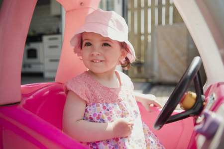 One little girl sitting outside in her toy car using her imagination. She is looking out of the window, smiling and enjoying herself. Stock Photo