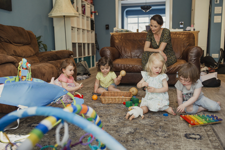 Small group of little girls playing with toys in the living room. One mid adult woman is stiiting watching and keeping an eye on them as they play together.