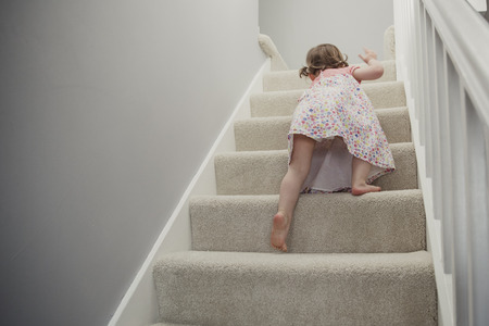 Rear view of a little girl climbing up the stairs in the house. She is exploring and going on an adventure around the house. Stock Photo