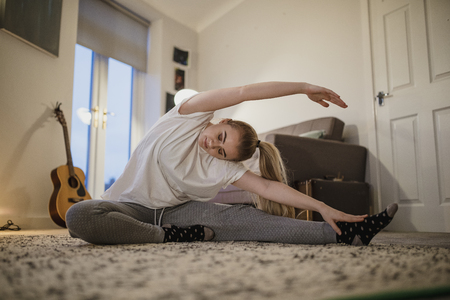 University student is doing yoga in her living room. 스톡 콘텐츠