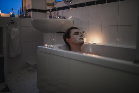 Young man is relaxing in the bath with a face mask on and candles lit around him. Stockfoto