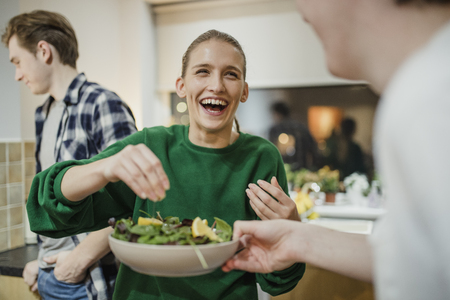 Young woman is laughing with her friends at a dinner party as she squeezes lemon juice on a salad.
