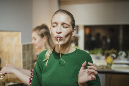 Young woman is posing for the camera with spaghetti hanging out her mouth. Reklamní fotografie