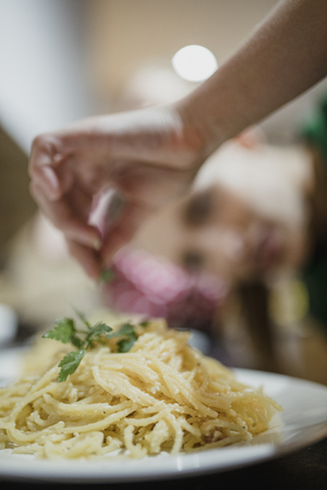 Close up shot of homemade spaghetti carbonara with coriander being added on top. Banco de Imagens