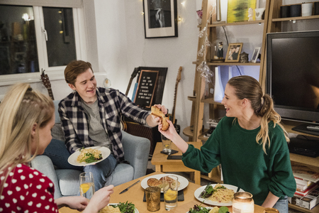 Young couple are at a home dinner party eating spaghetti carbonara. They are tearing garlic bread to share. Stock Photo
