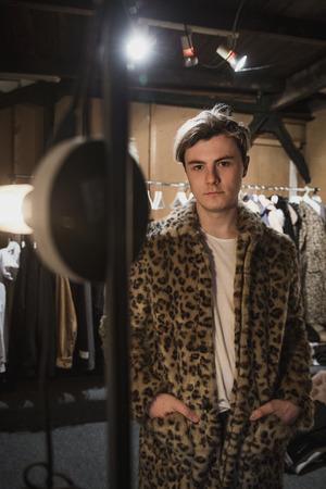 Fashion designer posing in a fur coat in his dressing room.