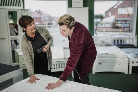 Une vendeuse aide un jeune homme à acheter un nouveau matelas. Elle lui parle pendant qu'il teste un écran.