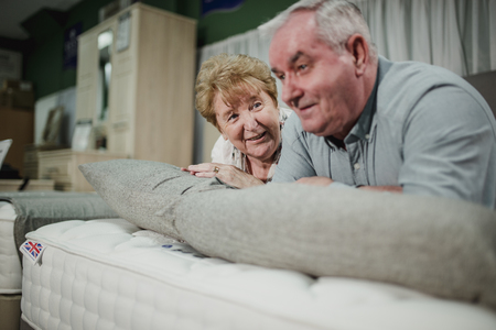 Senior couple are lying on a bed while shopping in a furniture shop.