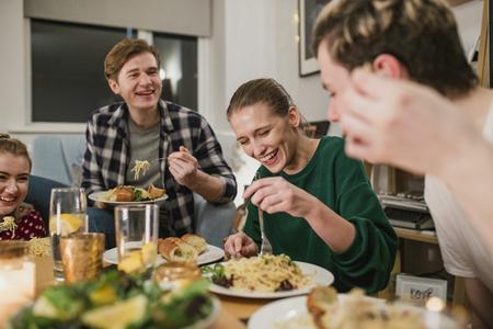 Des amis organisent un dîner à la maison. Ils rient en mangeant des spaghettis à la carbonara.