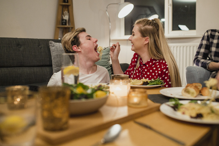 Young couple are at a dinner party and the girl is feeding her partner a big mouthful of spaghetti carbonara. Stock Photo