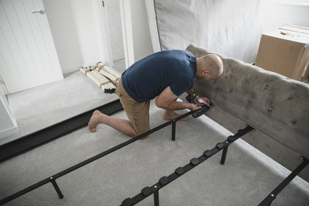 Mature man is using a power drill to put together a bed in his new home. Reklamní fotografie