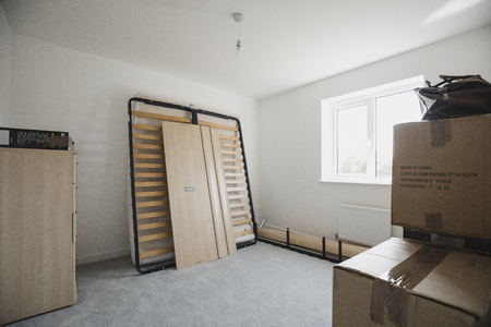 Bedroom of a new home with flatpack furniture and cardboard boxes.