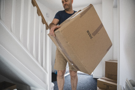 Mature man is moving boxes of belongings in to his new home.