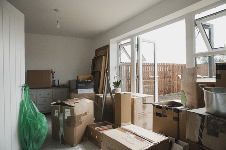 Dining room is full of furniture and cardboard boxes as a family are moving in. Stock Photo
