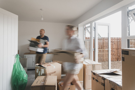 Slow shutter speed shot of a mature couple moving boxes in their new home.