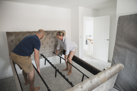 Mature couple are moving in to their new home. They are positioning their bed frame in the bedroom.