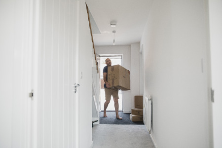 Mature man is carrying boxes in to his new home.