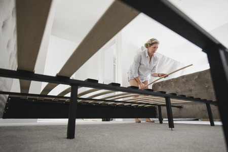 Low angle view of a mature woman setting up her bed in her new home. Banco de Imagens