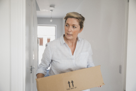 Mature woman is moving boxes in to her new home.