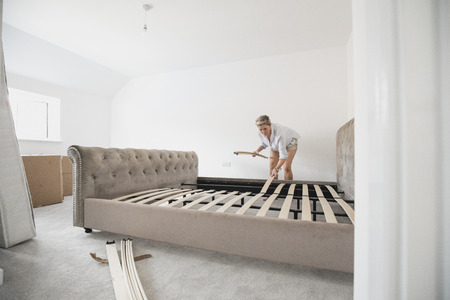 Mature woman is building her bed in her new home. She is placing wooden slats on the bed frame. Foto de archivo