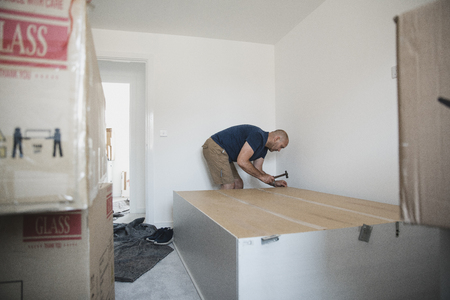 Mature man is putting a wardrobe together in a bedroom of a new home. Stock Photo