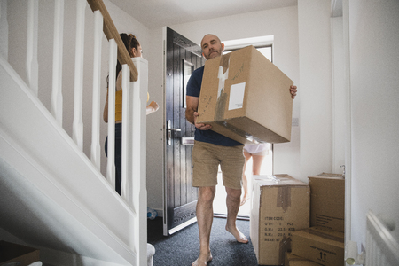 Mature man is carrying boxes in to his new home. His daughter and wife can be seen behind him. Stock Photo