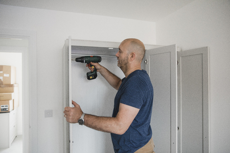 Mature man is building a wardrobe in the bedroom of his new home. Stock Photo