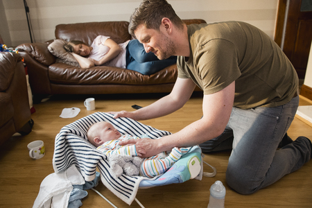 Father checking on his newborn baby boy as he wakes up from a sleep and tryig to keep quiet while his exhausted wife has a nap on the sofa. Stockfoto