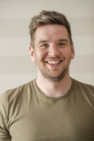 Mid-adult man in a green t-shirt smiling while looking at the camera for a portrait. Stock fotó