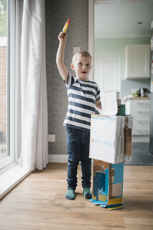 Little boy standing indoors next to a home made robot he has made out of old cardboard boxes. He is holding a rocket ice lolly and pretedning that it is flying. Banco de Imagens