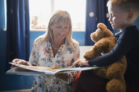 Grandmother and her grandson choosing a book to read before bedtime. The little boy is holding his teddy bear and pointing in the book. Stock Photo