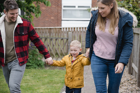 Little boy holding his parents hands as they walk along the garden path to get back to the house. They are smiling and laughing on the way back. Stock Photo