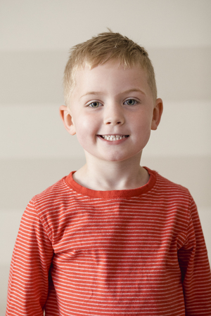 Little Boy in a red striped t-shirt smiling while looking at the camera for a portrait. Stock Photo