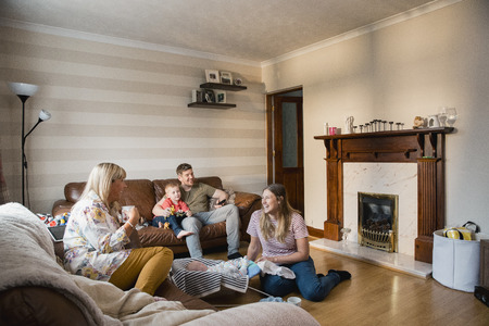 Young family are at home with their son and newborn baby and the grandmother is visiting them for tea. Stockfoto