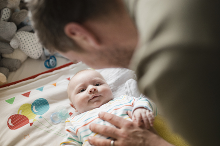 Mid-adult father checking up on his newborn baby boy while he is lying in his crib.