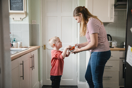 Little boy and his mother standing in the kicthen in the house. The little boys mother is holding a bowl of strawberries while the little boy takes some for a snack. Banco de Imagens - 109700341