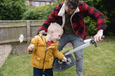 Little boy and his father playing in the front garden on the grass. They are playing with a toy sword and sheild. They are laughing and having fun together.