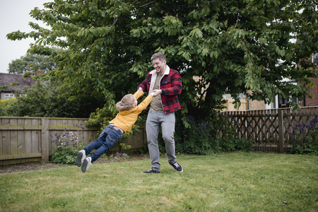 Little boy having fun with his father. The father is holding his sons hands and swinging him around while laughing and smiling. Stock Photo
