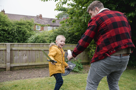 Little boy and his father playing in the front garden on the grass. They are playing with a toy sword and sheild. They are laughing and having fun together. Stock Photo - 110303986