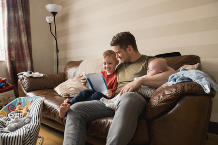 Mid-adult father is holding his newborn baby boy in his arm and then reading though the book with his son under the other arm. They all all sitting on the sofa in the living room.