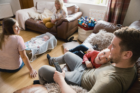 Three-generation family are relaxing, watching the tv and talking in the living room of their home.