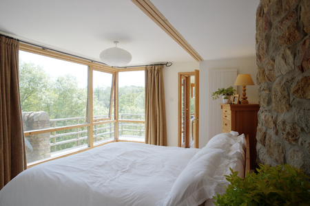 A wide view shot of a modern bedroom, a freshly made bed is against a brick wall, a view of trees on a bright day can be seen from the window. Stok Fotoğraf