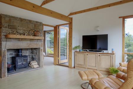 Una vista amplia del interior de una sala de estar cálida y acogedora, a la izquierda de la imagen hay una chimenea con leña cerca, y a la derecha una silla de cuero a la vista de un televisor moderno.