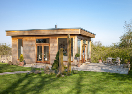 A wide view shot of a modern garden office on a bright summers day, a clear sky is above the wooden office and standing stones can be seen on the grass. Stok Fotoğraf