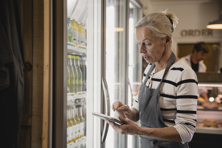 Mature coffee shop employee standing next to the fridges in the coffee shop performing a stock take.